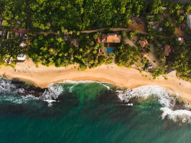 Verlaten strand bovenaanzicht tangalle sri lanka groene daken van gebouwen