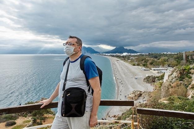 Verlaten strand in antalya, turkije, de europese toerist draagt een beschermend gezichtsmasker is
