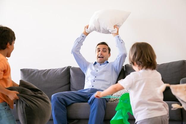 Verlaten vader zittend op de bank en met kussen boven het hoofd. gelukkige kinderen spelen met vader, vechten met kussens en samen plezier hebben thuis. jeugd-, vakantie- en spelactiviteitenconcept