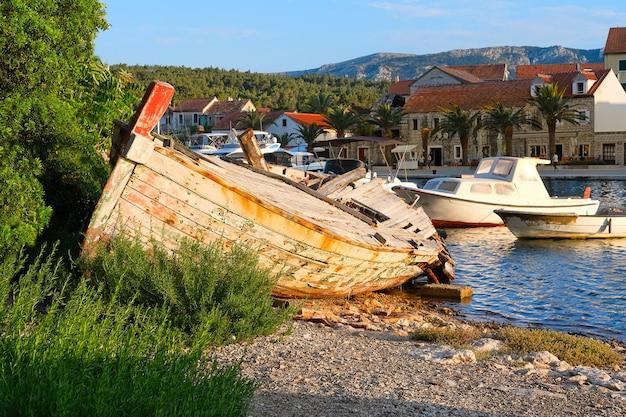 Verlaten vissersboot op wilde kust in vrboska-dorp op hvar, dalmatië, kroatië, europa.