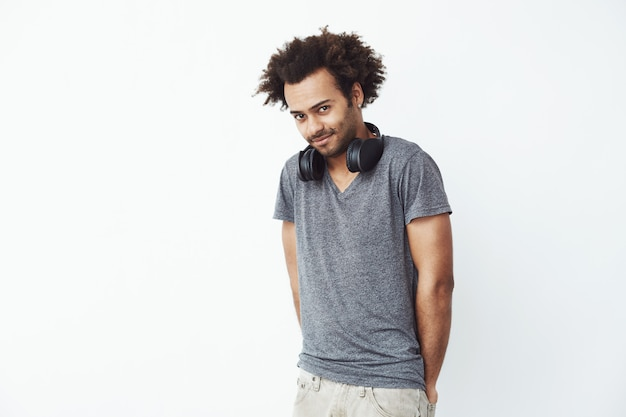 Verlegen afrikaanse man met koptelefoon glimlachen