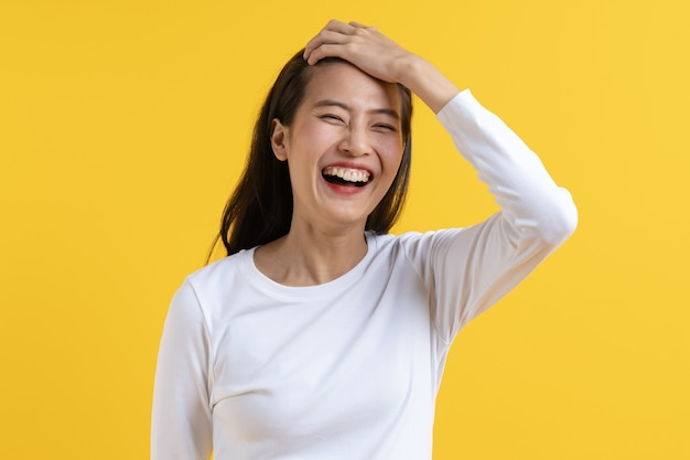 Verlegen aziatische jonge vrouw lachen geïsoleerd op gele achtergrond