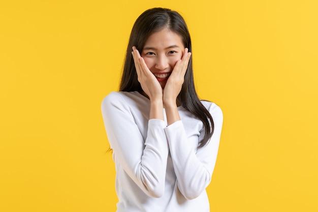 Verlegen aziatische vrouw in casual kleding die gezicht bedekt en gluren