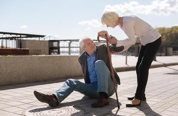 Verlegen bejaarde zieke man zittend op de grond en glimlachend terwijl fatsoenlijke vrouw zich zorgen maakte over deze man