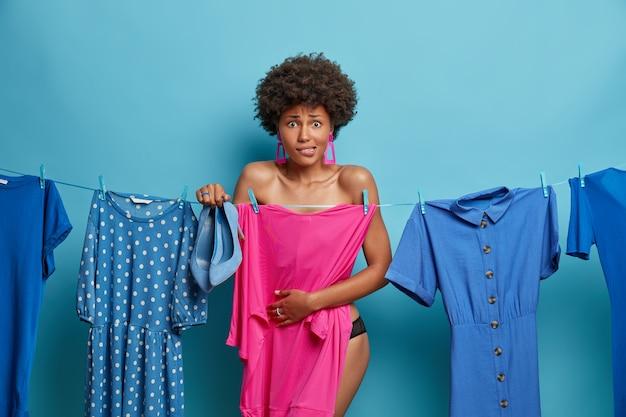 Verlegen bezorgde vrouw verbergt naakt lichaam, houdt schoenen met hoge hakken vast, staat voor moeilijke keuze wat ze aan moet, staat tegen blauwe muur. afro-amerikaanse vrouwen maken zich zorgen als ze te laat op hun werk komen, moeten zich snel kleden