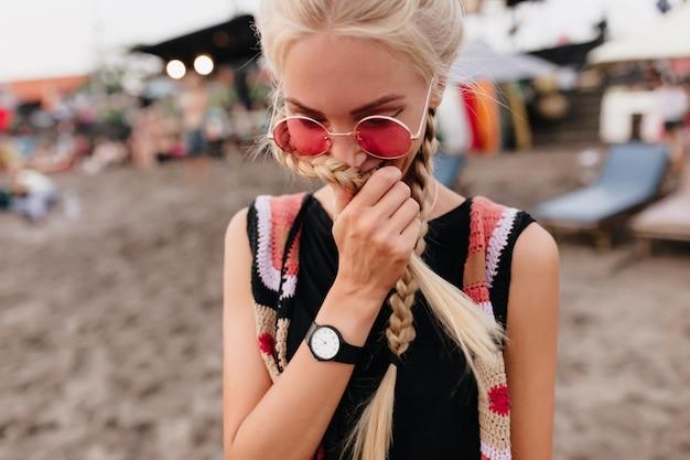 Verlegen blonde vrouw met vlechten die zich voordeed op het strand. openluchtportret van leuke blonde vrouw in roze zonnebril en zwarte tanktop.