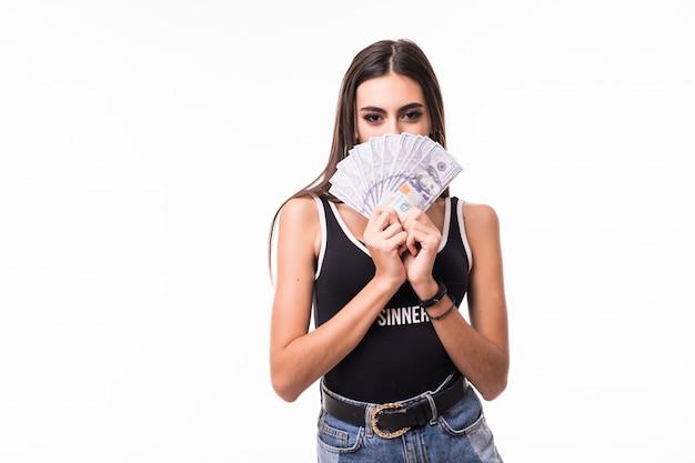 Verlegen brunette dame in korte spijkerbroek houdt fan van dollarbiljetten