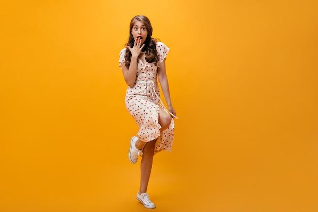 Verlegen dame in stijlvolle jurk bedekt haar mond van verbazing. geschokt stijlvolle vrouw met golvend kapsel in coole sneakers poseren.