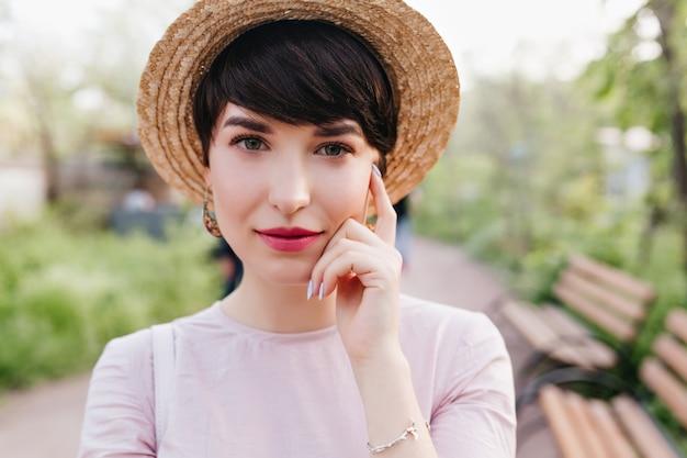 Verlegen donkerharige dame met rode lippen die zilveren armband dragen die haar gezicht met vinger aanraakt