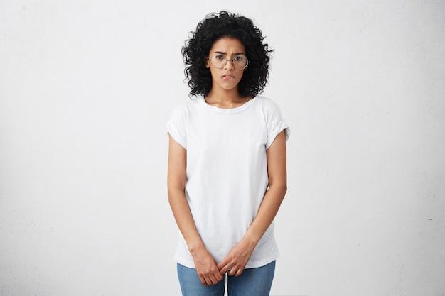 Verlegen en timide afrikaans amerikaans studentenmeisje dat een bril draagt