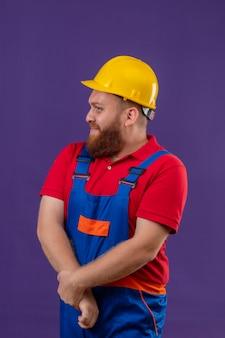Verlegen jonge bebaarde bouwersmens in bouwuniform en veiligheidshelm hand in hand samen op zoek opzij over paarse achtergrond