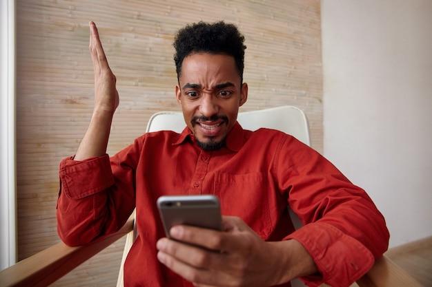 Verlegen jonge bruinogige kortharige, bebaarde man met donkere huid, verward op zoek op zijn mobiele telefoon en hand opsteken zittend in een stoel op interieur