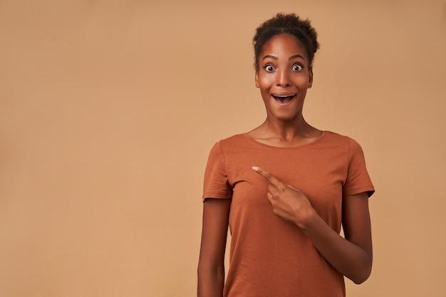 Verlegen jonge donkerhuidige krullende vrouw die verrast kijkt met grote ogen en mond open terwijl ze met wijsvinger opzij wijst, geïsoleerd op beige