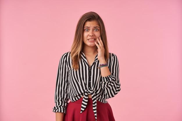 Verlegen jonge mooie brunette vrouw gekleed in feestelijke kleding aanraken van haar gezicht met opgeheven hand en ronding haar ogen met steenbolk, geïsoleerd op roze