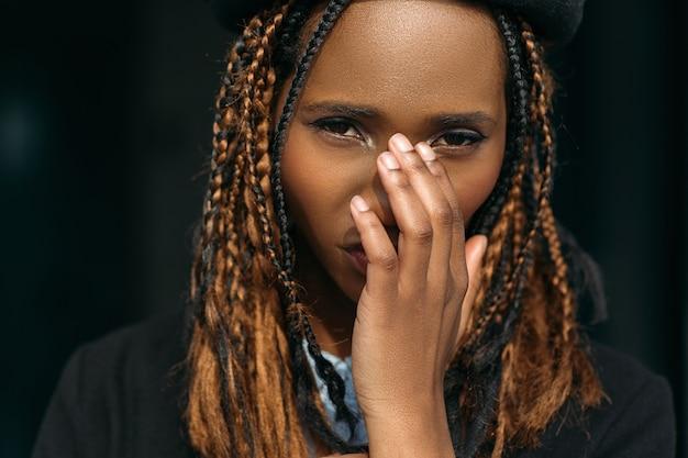 Verlegen jonge zwarte vrouw. beschaamd meisje. stijlvol kapsel, beschaamde mooie vrouw die haar gezicht bedekt op een donkere achtergrond, aarzeling concept
