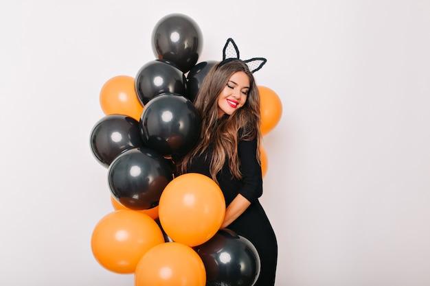 Verlegen langharige vrouw poseren met kleurrijke halloween ballonnen
