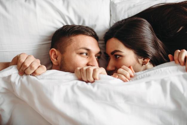 Verlegen liefdepaar ligt op een groot wit bed, bovenaanzicht.