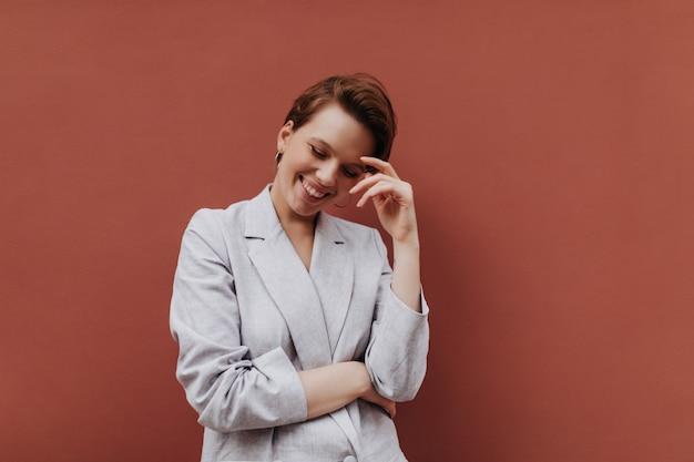 Verlegen meisje dat in grijze uitrusting op bruine achtergrond glimlacht. aantrekkelijke kortharige vrouw in oversized jasje lachen op geïsoleerde