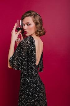 Verlegen meisje in trendy feestjurk kijkt over de schouder staande op een donkere achtergrond