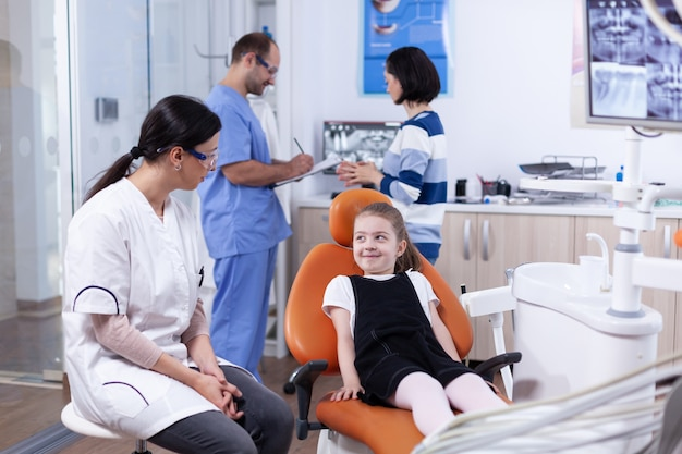 Verlegen meisje kijkend naar tandarts arts wachten tanden holte behandeling. kind met haar moeder tijdens tandencontrole met stomatolog zittend op een stoel.