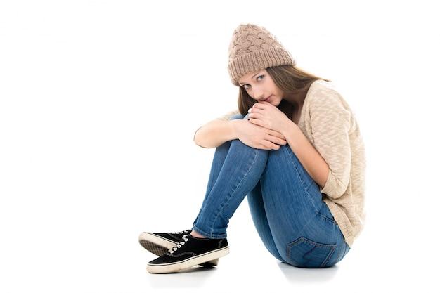Verlegen meisje, zittend op de vloer