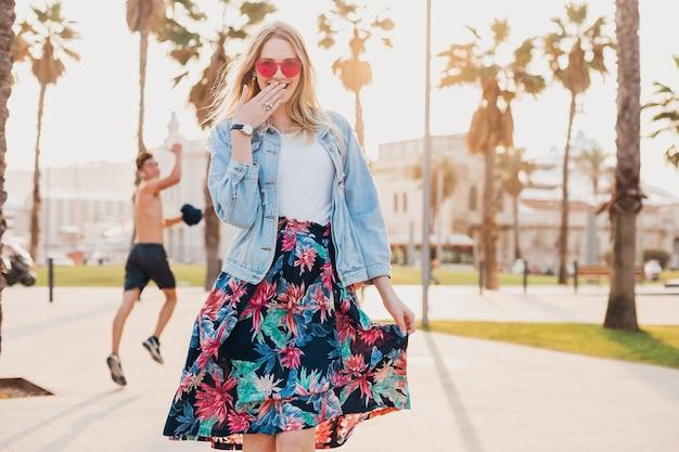 Verlegen mooie lachende vrouw flirten met man in romantische bui in stadsstraat in stijlvolle bedrukte rok en denim oversized jas met roze zonnebril