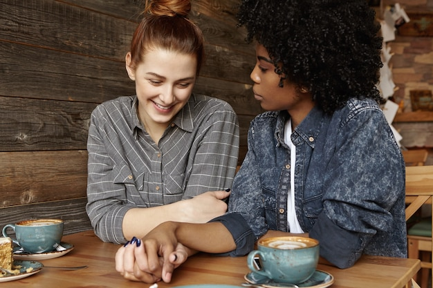 Verlegen mooie roodharige vrouw met haarbroodje glimlachend vreugdevol zittend bij coffeeshop
