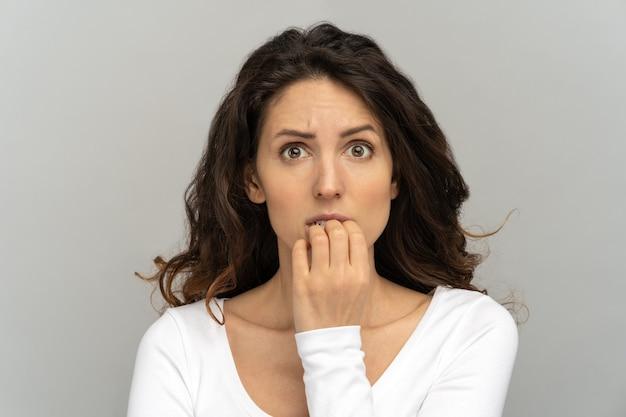 Verlegen, onhandige jonge vrouw die nagels bijt die zich beschaamd, verward en nerveus voelt, terwijl ze naar de camera kijkt.