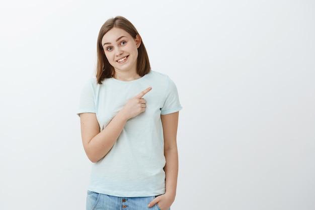 Verlegen schattig onbezorgd brunette sportvrouw in trendy t-shirt bukken kantelend hoofd en glimlachend vriendelijk en trots wijzend naar de rechterbovenhoek toont haar medailles poseren over witte muur