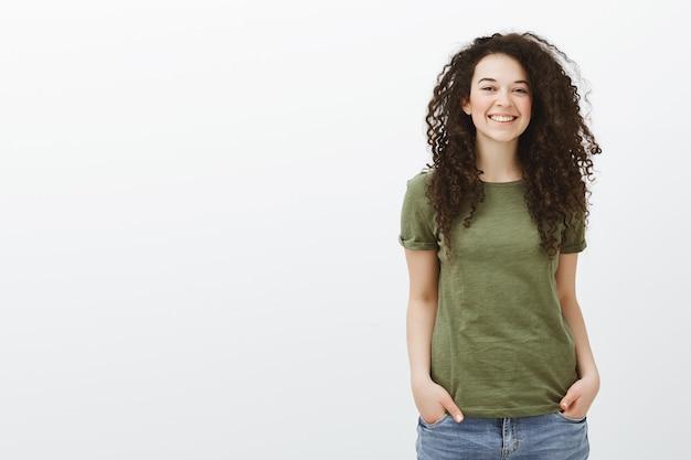Verlegen schattige krullende vrouwelijke student in donkergroene t-shirt