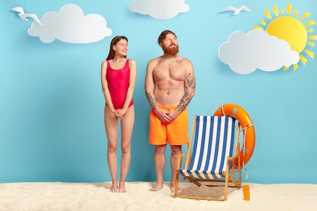 Verlegen tevreden vrouwelijke en mannelijke toerist, kijk met plezier opzij, houd handen bij elkaar, vrouw draagt rode bikini