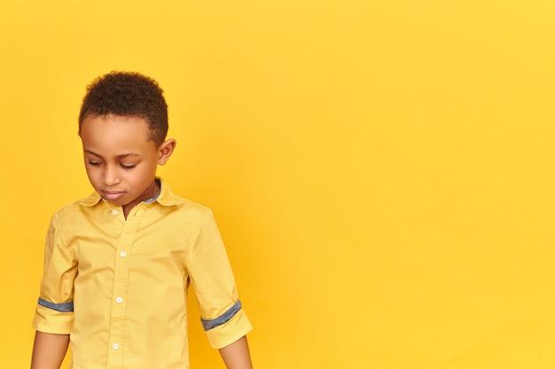 Verlegen timide kleine afrikaanse jongen wordt beschaamd naar beneden te kijken, schaamt zich voor slecht gedrag geïsoleerd op lege gele muur