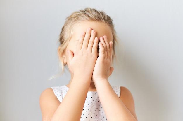 Verlegen timide meisje bedekt gezicht, bang. vrouwelijke jongen in verlegenheid gebracht poseren geïsoleerd met handen op haar ogen, huilen, zich schamen omdat moeder haar vertelt. baby speelt verstoppertje