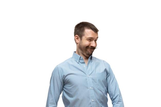 Verlegen, uitlachen. jonge man met grappige, ongebruikelijke populaire emoties en gebaren geïsoleerd op een witte studio achtergrond. menselijke emoties, gezichtsuitdrukking, verkoop, advertentieconcept. trendy look geïnspireerd op memes.