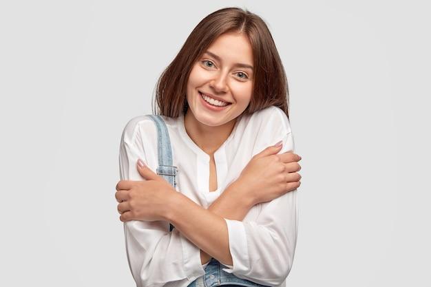 Verlegen vrolijk meisje omhelst zichzelf, drukt positieve emoties uit, voelt zich verheugd om compliment of lof te ontvangen, gekleed in een stijlvol shirt
