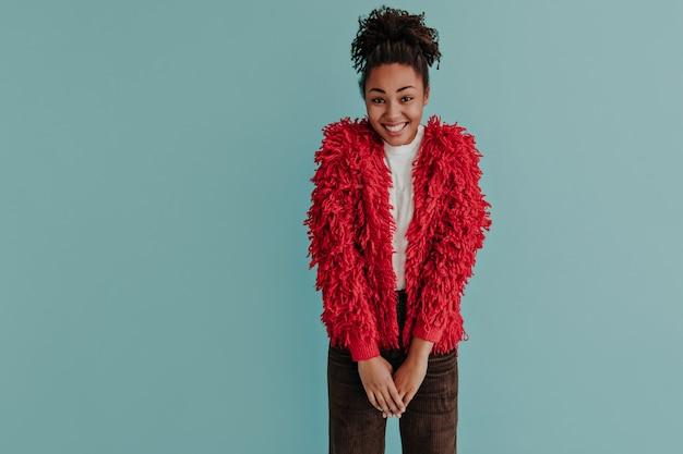 Verlegen vrouw die in rood jasje voorzijde bekijkt