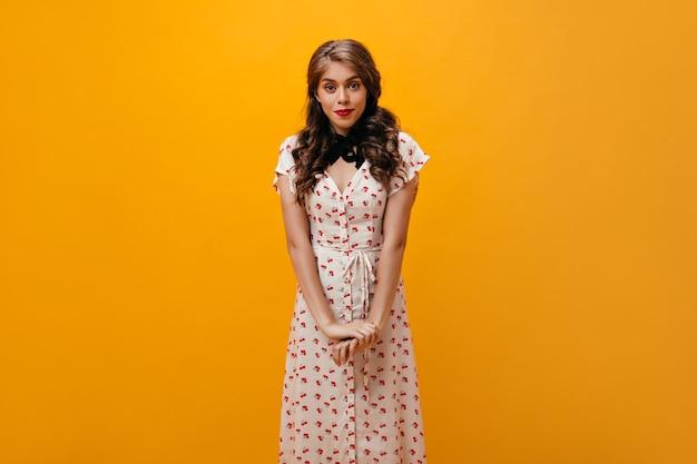 Verlegen vrouw in bloemenprint jurk vormt op een oranje achtergrond. vrij jong meisje met krullend meisje in stijlvolle kleding op zoek naar camera.