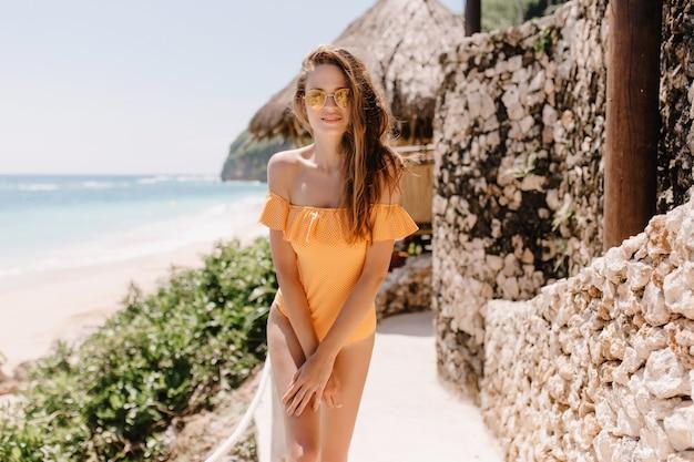 Verlegen wit vrouwelijk model in zonnebril poseren in exotische resort in de ochtend. schattige caucasain vrouw in stijlvolle oranje zwembroek staande in de buurt van stenen hek