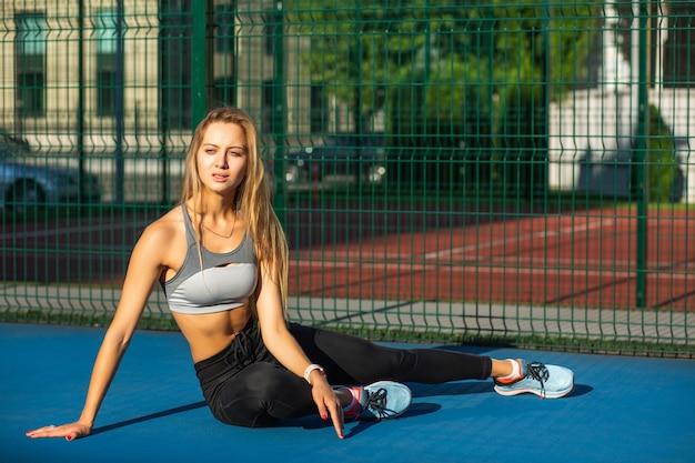 Verleidelijk blond model met perfect lichaam in sportkleding poserend bij het hek op de tennisbaan