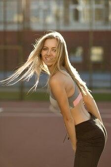 Verleidelijk fitnessmodel met haar in de wind poseren op een tennisbaan in zonnestralen