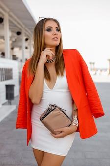 Verleidelijke blonde europese vrouw in rode jas en witte jurk poseren op straat. hand bij het gezicht, lang ooglid.