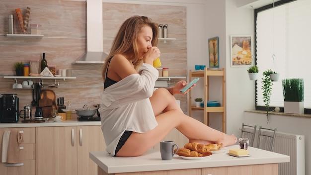 Verleidelijke blonde huisvrouw sms't en drinkt hete koffie in zwarte lingerie die 's ochtends op de keukentafel zit. provocerende jonge vrouw met tatoeages in verleidelijk ondergoed ontspannen.