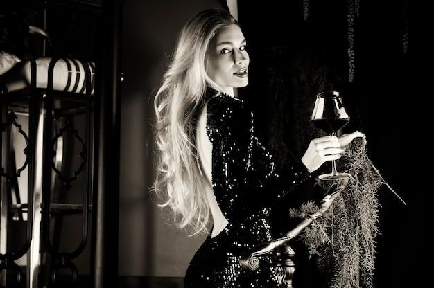 Verleidelijke blonde in een groene avondjurk poseren met een glas rode wijn. gemengde media