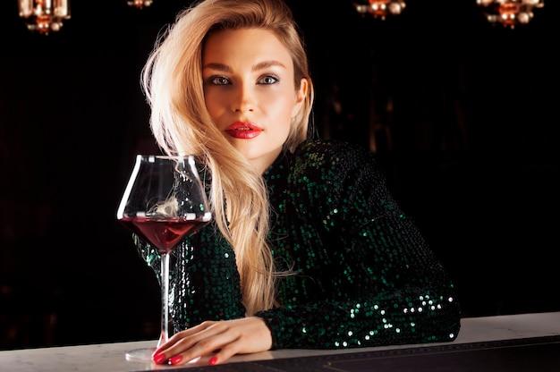 Verleidelijke blonde in een groene avondjurk poseren met een glas rode wijn.