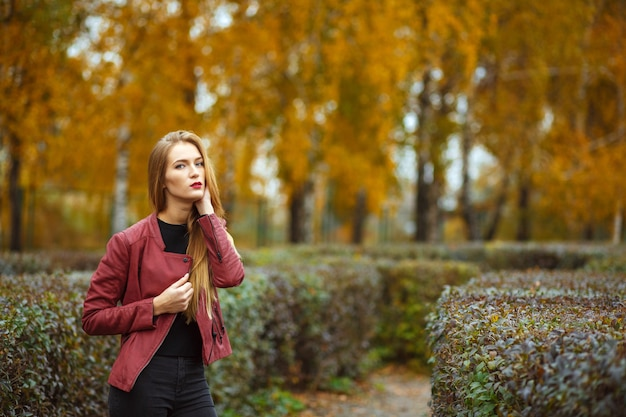Verleidelijke blonde vrouw met rode lippen, gekleed in een rode jas die zich voordeed in de herfsttuin. ruimte voor tekst