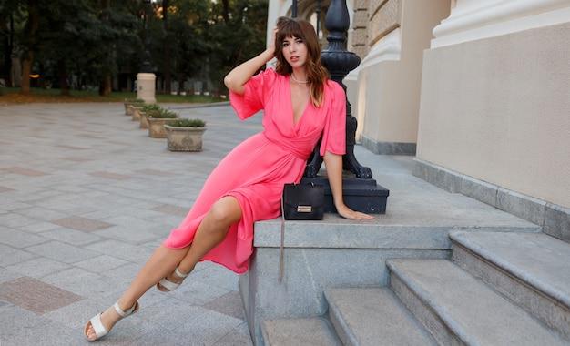Verleidelijke brunette vrouw in roze jurk poseren buiten in oude europese stad.