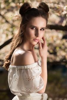 Verleidelijke brunette vrouw poseren in de buurt van de bloeiende magnoliaboom in witte kanten jurk