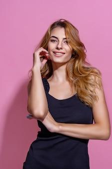 Verleidelijke charmante vrouw in zwarte jurk op roze achtergrond glimlachend met lang bruin haar kijkend naar...