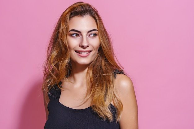 Verleidelijke charmante vrouw in zwarte jurk op roze achtergrond glimlachend met lang bruin haar wegkijkend