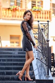 Verleidelijke dame in korte lederen jurk die de trap afloopt